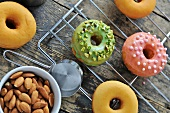 Doughnuts topped with glaze, pistachios, sugar balls and almonds