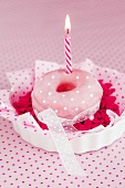 A doughnut with pink glaze and a candle