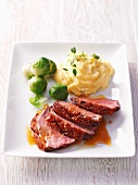 Duck breast with orange sauce, mashed potatoes and Brussels sprouts