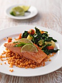 A fillet of salmon with red lentils and vegetables
