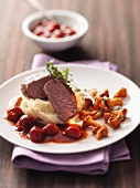 Venison steak on apple mashed potatoes with cherry sauce and chanterelle mushrooms