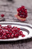 Pomegranate seeds on a silver plate and a piece of pomegranate