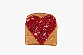Slice of Bread with Peanut Butter and a Jelly Heart; White Background