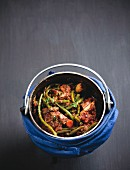 Italian pot roast with lamb and beans in a potjiekos cooking pot
