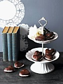 Chocolate hearts with cream filling, next to and on a tiered cake stand