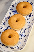 Three doughnuts on a blue and white plate