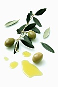 A olive sprig with olives next to a pool of olive oil