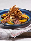 Liver with orange fillets and crispy onion rings on potato straw