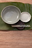 Bowls, plates and chopsticks on a banana leaf (Asia)