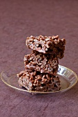 Three chocolate rice crispy cakes on a glass plate