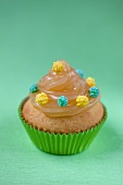 A cupcake decorated with lemon curd and sugar pearls