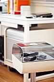 Abgerundete weiße Kunststoffvitrine mit Plexiglashaube für verschiedene Kameras; im Hintergrund unscharf ein Schreibtischplatz