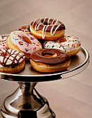 Assorted Frosted Donuts on a Silver Pedestal Dish