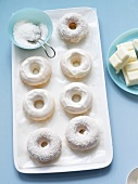 White Chocolate and Coconut Covered Doughnuts; Bowl of Coconut and Chunks of White Chocolate