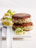 Freshly made burgers with a potato and cucumber salad