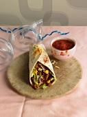 A burrito with a tomato dip - hangover breakfast