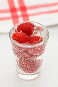 Raspberries in a glass of water