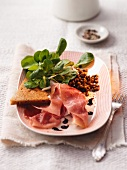 Lentil salad with raw ham and bread