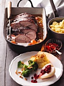 Roast wild boar with mashed potatoes, broccoli and lingonberry pears