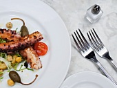 Fried octopus with cherry tomatoes, giant capers and chickpeas