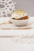 A wintry cupcake decorated with frosting and golden sugar balls