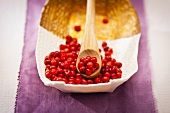 Pink peppercorns in a bowl and on a wooden spoon