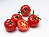 Four whole tomatoes and a halved tomato on a white surface
