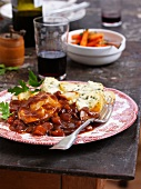 Coq au vin with a potato and herb gratin on a plate