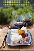 A cheese platter with sausage, red wine and a baguette