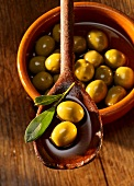 Green olives in olive oil on a wooden spoon and in a clay dish