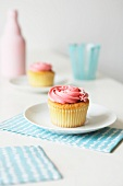Cupcake with strawberry icing and silver balls