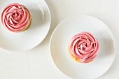 Two cupcakes decorated with strawberry cream and silver balls