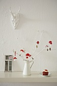 A twig decorated with toadstools and cupcakes against a wall hung with a hunting trophy