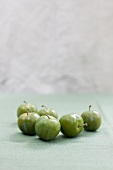 Greengages on a green cloth