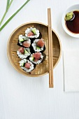 A steamer filled with tuna and cucumber sushi, with soy sauce and wasabi paste