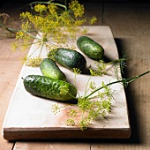 Gherkins and dill flowers on a wooden board