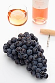 Rose wine, red grapes and a cork screw