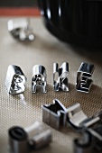 Cookie cutters spelling the word BAKE