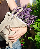 A woman holding a linen bag with lavender flowers