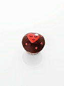 A cupcake decorated with hearts