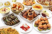 Chicken, stuffed vine leaves and mini burgers on a buffet