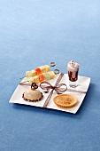 Dessertteller mit Obstspiess, Petit Four, Törtchen und Schokocreme