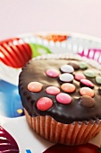 A cupcake decorated with chocolate glaze and colourful chocolate beans