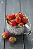 Fresh strawberries in an old measuring cup