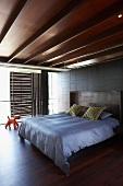Schlafzimmer mit edler Holzdecke und sonnengeschützter Glasfront durch verschiebbare Holzpaneele; in der Mitte ein großes Doppelbett