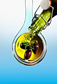 Olive oil being poured over olives
