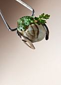 A stuffed snail being picked up with a pair of tongs