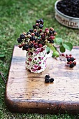 Wild blackberries in a small milk jug on a wooden board