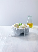 Mozzarella and olive oil in bowl lined with a muslin cloth