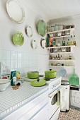 Sonnige Küche mit Retro-Herd und Keramiktellersammlung in Weiß und Grün an der Wand